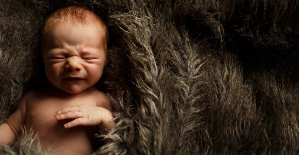 Newborn baby about to cry wrapped up in fur