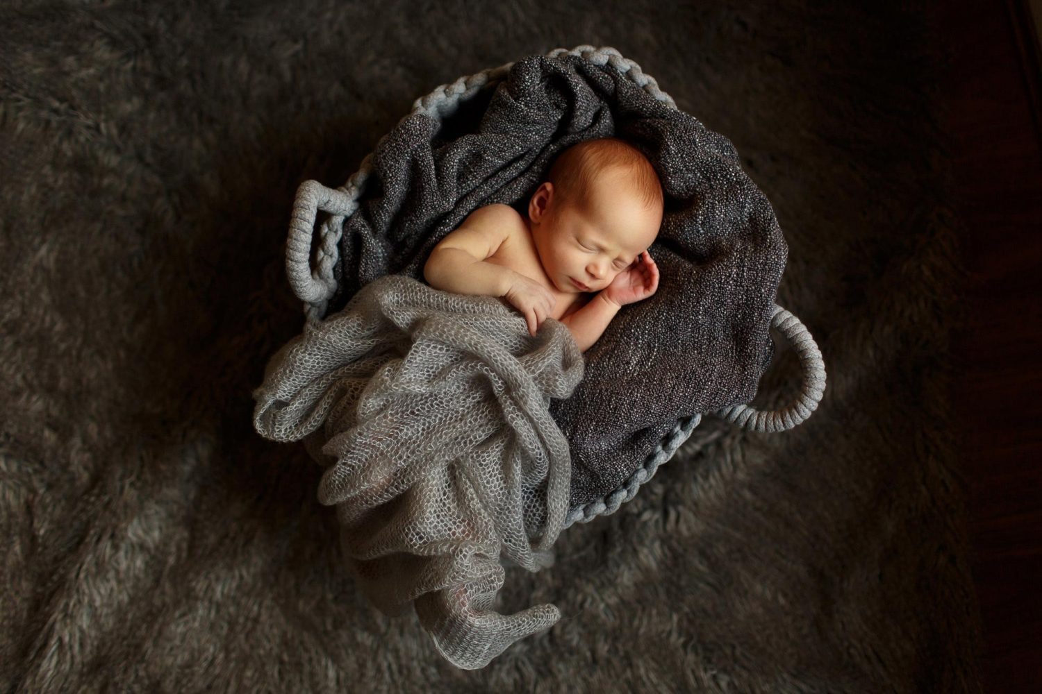 newborn baby girl tucked up in a grey basket
